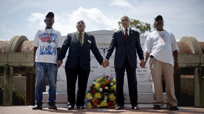 """Civil rights activists and Southern Christian Leadership Conference members from left, Ralph Worrell, Dr. Bernard Lafayette, Jr., C.T. Vivian and Frederick Moore, join hands during the singing of """"We Shall Overcome"""" after laying a wreath at the gravesite of Rev. Martin Luther King Jr., marking the 44th anniversary of his assassination, Wednesday, April 4, 2012, in Atlanta. (AP Photo/David Goldman)"""