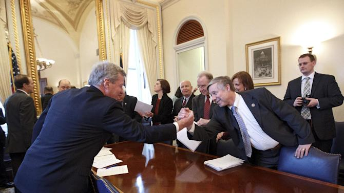 FILE - In this Feb. 16, 2012, file photo Senate Finance Committee Chairman Sen. Max Baucus, D-Mont., left, reaches across the table to shake hands with Rep. Fred Upton, R-Mich., after bi-partisan House and Senate conferees signed a compromise agreement on the payroll tax cut extension. Democrats and Republicans are forcing votes in Congress this week in April 2012 on competing tax plans that they know are doomed from the start. But little does that matter to either party. (AP Photo/J. Scott Applewhite, File)