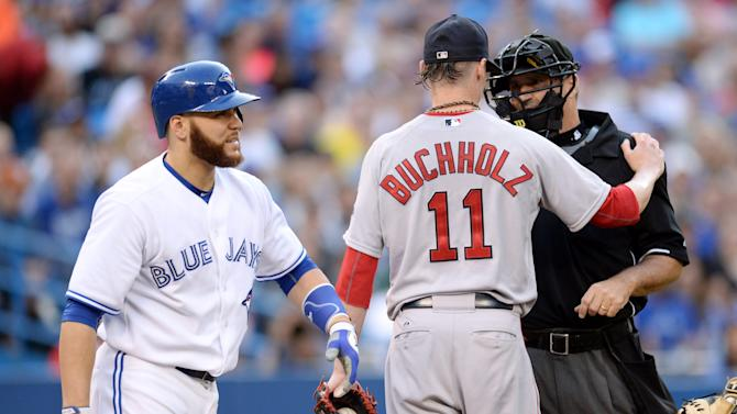 Toronto Blue Jays' Russell Martin, left, walks to first base after being hit by a pitch as Boston Red Sox starting pitcher Clay Buchholz, center, talks to home plate umpire Tony Randazzo during the second inning of a baseball game in Toronto, Monday, June 29, 2015. (Frank Gunn/The Canadian Press via AP) MANDATORY CREDIT