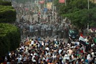 Egyptian demonstrators confront riot police during protests outside the defense ministry in Cairo&#39;s Abbassiya district. Egypt&#39;s ruling military announced a curfew in the area surrounding the defence ministry in central Cairo, after fierce clashes between troops and anti-military protesters there