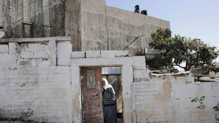 A Palestinian woman stands at the entrance to her house in the Shuafat refugee camp in the West Bank near Jerusalem