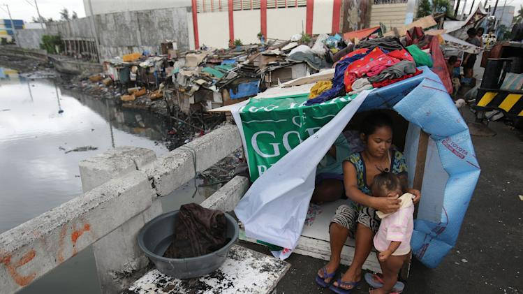 A Filipino family stays in an improvised shelter as strong waves during heavy rainfall shattered their makeshift home built under a bridge at a slum area in Manila, Philippines on Thursday,July 31, 2014. Tropical Storm Nakri, locally called Inday, continues to move in the north, northwest direction out of the Philippines as it enhances the southwest monsoon causing occasional rains in some parts of the country including the capital, according to a report from the Philippine Atmospheric, Geophysical and Astronomical Services Administration. (AP Photo/Aaron Favila)