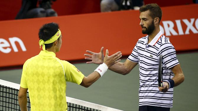 Benoit Paire of France shakes hands with Japan's Kei Nishikori after defeating him during their men's singles semifinal match at the Japan Open tennis championships in Tokyo