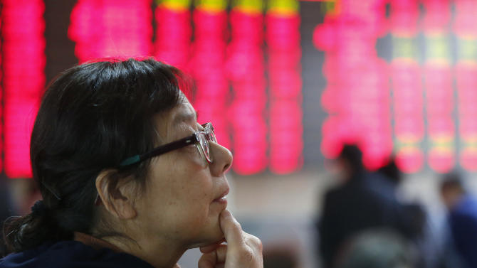 An investor looks at the stock price monitor at a private securities company Tuesday, Dec. 3, 2013, in Shanghai, China. Asian stock markets outside Japan mostly slid Tuesday as investors awaited a slew of U.S. economic data this week to gauge when the Federal Reserve will start reducing its monetary stimulus. (AP Photo)