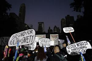 Occupy Wall Street protesters hold up placards in Bryant Park in New York September 17, 2013. REUTERS/Joshua Lott