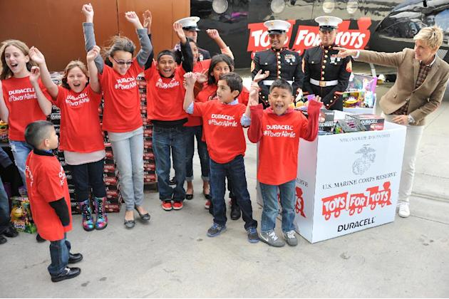 "Ellen DeGeneres, far right, with U.S. Marines and her helpers attend the Ellen DeGeneres officially launches the Duracell ""Power a Smile"" Program, on Friday, Nov. 22, 2013, at Van Nuys Airport in Los"