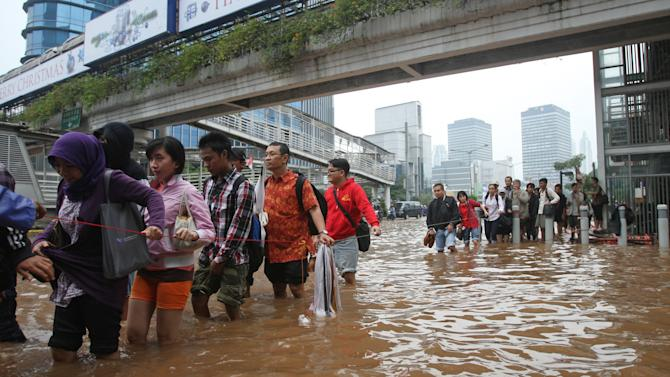 People cross a flooded street while holding a cord for safety in Jakarta, Indonesia Friday, Jan. 18, 2013. Indonesia's army deployed rubber boats in the capital's business district on Thursday to rescue people trapped in floods that inundated much of the city of 14 million people. (AP Photo/Achmad Ibrahim)