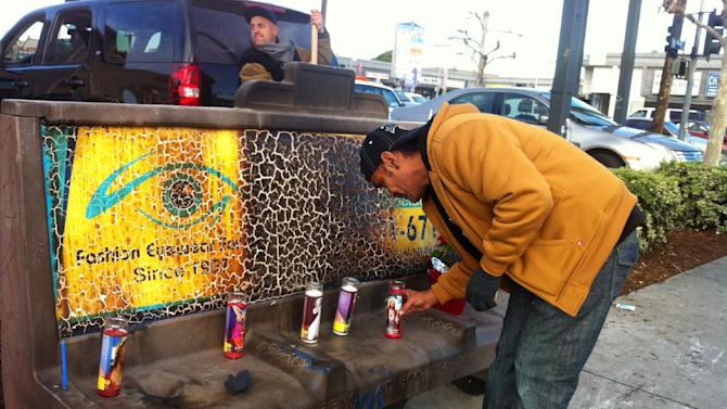 Phil Furtado places candles on a burned city bus bench in Los Angeles on Thursday Dec. 27,2012. Police arrested a man for allegedly setting a 67-year-old woman on fire who was sleeping on the bus stop bench.  A witness said he saw a man come out of the store and pour something on the woman who had been sleeping on a bench before striking a match and setting her ablaze. The woman, who may be homeless, was taken to a hospital and listed in critical condition. (AP Photo/Greg Risling)