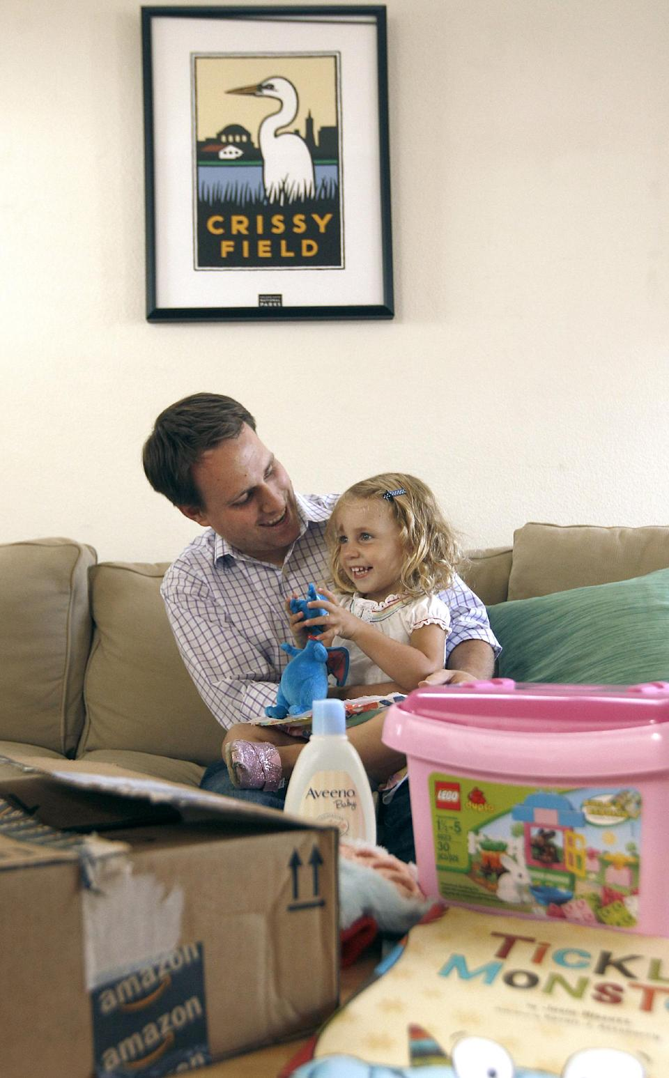 Reid Butler plays his daughter Siena, 2, as they pose for photographs with recent online purchases from Amazon at their home in Walnut Creek, Calif., Thursday, Sept. 13, 2012. Products are flying off the shelves at Amazon warehouses across the county as Californians prepare to start paying sales taxes on online purchases. (AP Photo/Jeff Chiu)