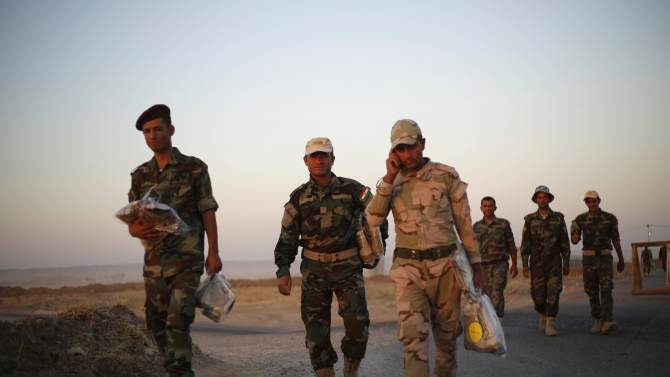 Kurdish Peshmerga fighters holding new sets of uniforms head to the front line to battle the Islamic State, in Gwar