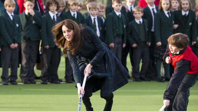 """Kate, the Duchess of Cambridge, centre,  plays hockey during her visit to St. Andrew's School, where she  attended school from 1986 till 1995, in Pangbourne, England, Friday, Nov. 30, 2012. The Duchess of Cambridge has gone back to school. The royal, formerly known as Kate Middleton, played hockey and revealed her childhood nickname — Squeak — when she returned to her elementary school for a visit Friday. Kate told teachers and students at the private St. Andrew's School in southern England that her 10 years there were """"some of my happiest years."""" She said that she enjoyed it so much that she had told her mother she wanted to return as a teacher. (AP Photo/Arthur Edwards, Pool)"""