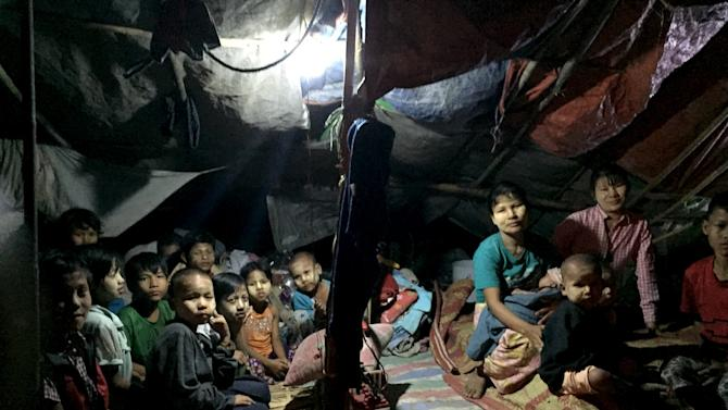 Homeless people watch a movie in a temporary shelter beside a street in Yangon