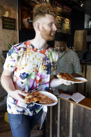 In this Wednesday, Sept. 12, 2012 photo, Brian Dwyer serves up a costumer's order at Pizza Brain in Philadelphia. Hundreds of people turned out for the grand opening of Pizza Brain this month in Philadelphia's Fishtown neighborhood. It's a restaurant where visitors can eat a slice or two of artisan pie while gawking at a pizza-related photos, records, knickknacks and videos.  (AP Photo/Matt Rourke)