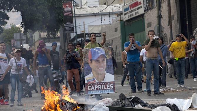 Demonstrators, one holding a poster of opposition presidential candidate Henrique Capriles, confront riot police from behind a burning barricade in the Altamira neighborhood in Caracas, Venezuela, Monday, April 15, 2013. National Guard troops fired tear gas and plastic bullets to disperse demonstrators protesting the official results in Venezuela's disputed presidential election.(AP Photo/Ramon Espinosa)