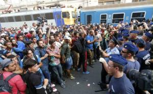 Migrants face Hungarian police in the main Eastern…