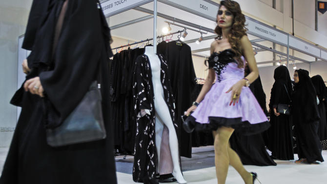 In this Saturday, April 13, 2013 photo, a woman in miniskirt passes the Princesses Touch abaya stand, selling designer abayas during a bridal exhibition in Dubai, United Arab Emirates. Just a few years ago, Gulf Arab women usually only felt comfortable showing off their fashion sense at ladies-only parties or family gatherings. In public, at least in their home countries, the standard all-black abaya _ a simple floor-length covering and accompanying head scarf _ was the only culturally accepted option. But now a new generation of abaya designers are giving the traditional garment a twist with choices of fabric, designs and even some expensive bling to allow Gulf women a host of style options. (AP Photo/Kamran Jebreili)