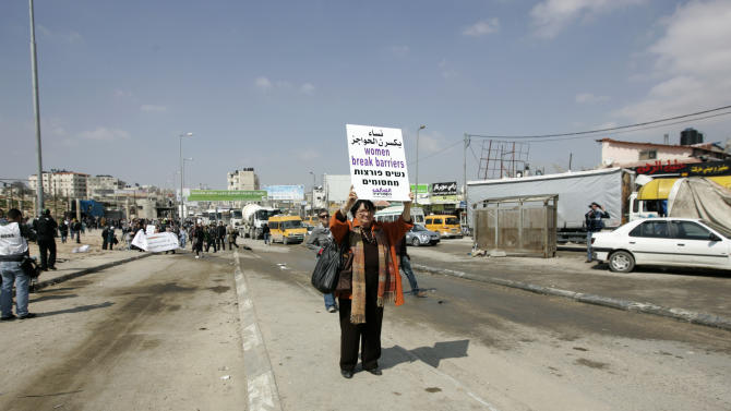 Activists attend a rally marking International Women's Day and call for the release of Palestinian prisoner Hana Shalabi, who has gone without food for 22 days, at Kalandia checkpoint between Jerusalem and the West Bank city of Ramallah, Thursday, March 8, 2012. Palestinians demanding the release of a hunger-striking detainee have clashed with Israeli troops at a West Bank crossing into Jerusalem.(AP Photo/Majdi Mohammed)