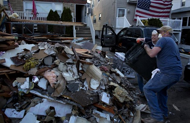 Volunteer Ashling Coleman and her husband Jerry Coleman of New York throw out the last load of debris for the day from the home of John and Ann Garvey, background left, which was damaged in the Rockaw