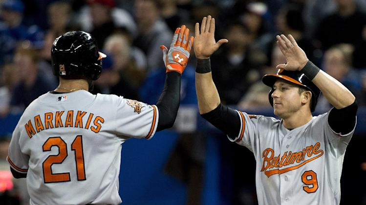 Baltimore Orioles' Nick Markakis (21) celebrates with David Lough (9) after scoring a run on a single by Chris Davis against the Toronto Blue Jays during the seventh inning of a baseball game in Toronto on Thursday, April 24, 2014. (AP Photo/The Canadian Press, Nathan Denette)