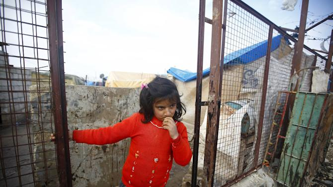 An internally displaced Syrian girl stands at a refugee camp near the Bab al-Salam crossing, opposite the Turkish province of Kilis