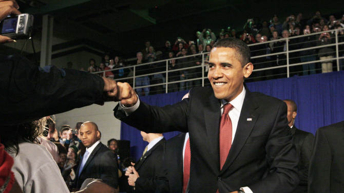 FILE - In this Feb. 9, 2009, file photo, President Barack Obama fist bumps with an audience member as he arrives for a town hall style meeting at Concord Community High School in Elkhart, Ind.  Though the knuckle-tapping action has been around for years, fist bump's place in popular culture was cemented by President Obama and First Lady Michelle Obama when Obama accepted the 2008 Democratic nomination, and now has earned a spot in the Merriam-Webster Collegiate Dictionary.  (AP Photo/Charles Dharapak, File)
