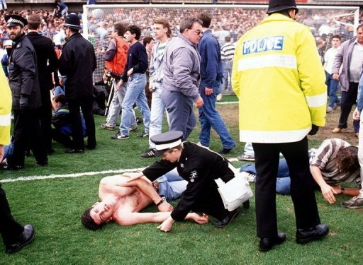 <p>Police rescue soccer fans at Hillsborough stadium April, 15, 1989, after 96 fans were crushed to death and hundreds injured when support railings collapsed during a match between Liverpool and Nottingham Forest. Families of those killed in the Hillsborough football stadium disaster will Monday demand new inquests</p>
