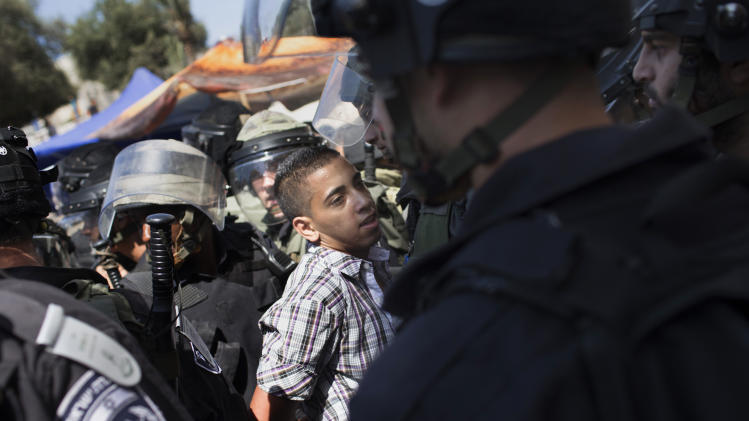 Israeli police detain a Palestinian demonstrator during a protest in Jerusalem, Friday, Sept. 14, 2012 as part of widespread anger across the Muslim world about a film ridiculing Islam's Prophet Muhammad. (AP Photo/Bernat Armangue)