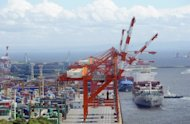 A freighter (R) comes in to dock alongside a container wharf in Tokyo port. Japan logged a bigger-than-expected trade deficit of about $11.5 billion in May as the nation's energy costs soared, official data showed Wednesday