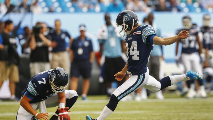 Argonauts kicker Waters kicks a field goal with place holder Harris against the Stampeders during their CFL football game in Toronto