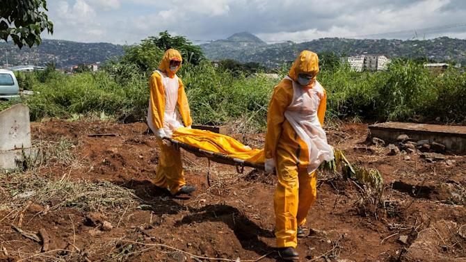 A team of funeral agents specialised in the burial of  victims of the Ebola virus carry a body prior to putting it in a grave at the Fing Tom cemetery in Freetown, on October 10, 2014