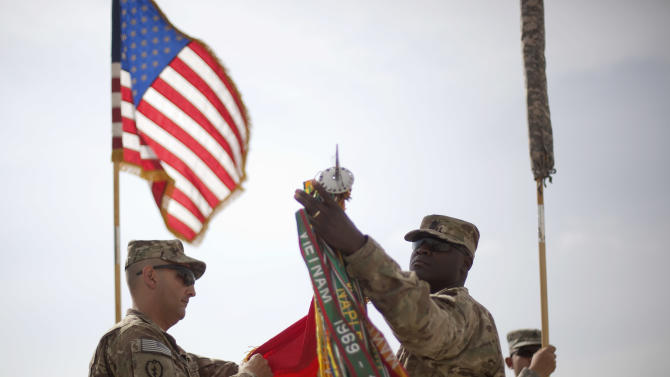 Lt. Col. Christopher Cardoni, left, and Command Sgt. Maj. Jerome Sligh, with the U.S. Army's 1st Battalion, 77th Field Artillery Regiment, 172nd Infantry Brigade out of Grafenwoehr, Germany, unveil their battalion flag Friday, Aug. 5, 2011 as they assume authority of the combat area from the 4th Brigade Combat Team, 101st Airborne Division out of Fort Campbell, Ky., during a ceremony at Forward Operating Base Sharana in Paktika province, Afghanistan. (AP Photo/David Goldman)