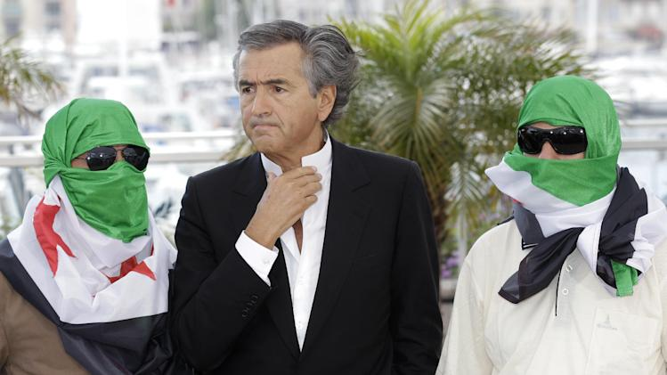 Director Bernard-Henry Levy, centre, flanked by two unidentified persons wearing Syrian flags pose during a photo call for The Oath of Tobruk at the 65th international film festival, in Cannes, southern France, Friday, May 25, 2012. (AP Photo/Lionel Cironneau)