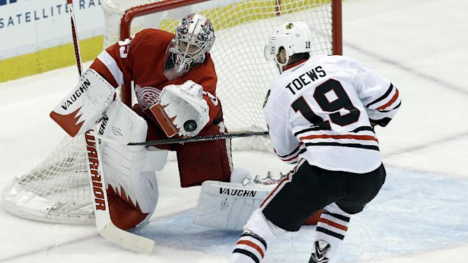 Detroit Red Wings goalie Jimmy Howard stops a Chicago Blackhawks center Jonathan Toews (19) shot during the second period in Game 4 of the Western Conference semifinals in the NHL hockey Stanley Cup playoffs in Detroit, Thursday, May 23, 2013. (AP Photo/Paul Sancya)