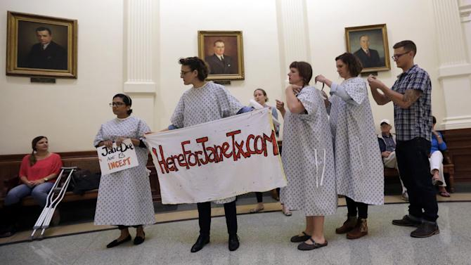 Activists tie on hospital gowns as they prepare to protest House Bill 3994 in the rotunda of the Texas Capitol, Friday, May 22, 2015, in Austin, Texas. Part of the bill would require women to present a government-issued ID before receiving abortion services. (AP Photo/Eric Gay)