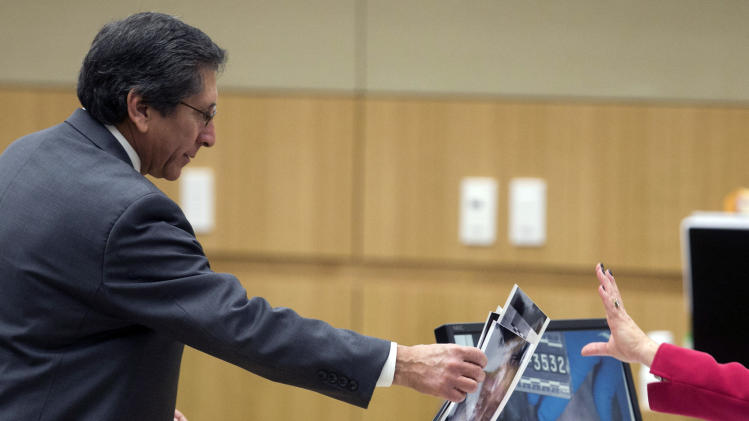 Prosecutor Juan Martinez hands autopsy photographs to the defense during the trial of Jodi Arias in Maricopa County court Tuesday, Jan. 8, 2013, in Phoenix. Arias is charged with murder in the death of her boyfriend, Travis Alexander, and prosecution is seeking the death penalty. (AP Photo/The Arizona Republic, David Wallace)