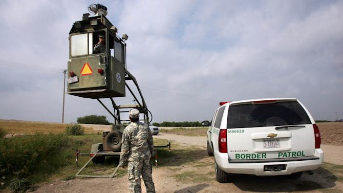 FILE - In this April 19, 2011, file photo, a member of the National Guard checks on his colleague inside a Border Patrol Skybox near the Hidalgo International Bridge in Hidalgo, Texas. An unprecedented surge of children caught trudging through South Texas scrublands or crossing at border ports of entry without their parents has sent government and nonprofit agencies that handle their shelter, legal representation and reunifications scrambling to expand their services. (AP Photo/Delcia Lopez, File)