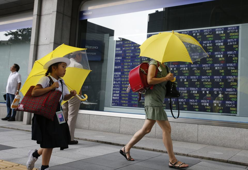 People walk past an electronic stock indicator in Tokyo, Monday, July 8, 2013. Concern over China's slowdown weighed on Asian stock markets Monday after the head of the International Monetary Fund warned of a loss of momentum in emerging economies. (AP Photo/Shizuo Kambayashi)