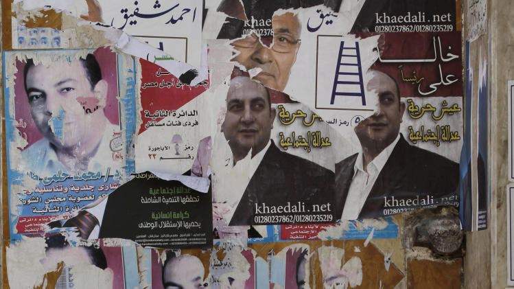 An Egyptian street vendor sells fruits in front of a wall filled with defaced posters of presidential candidates in Cairo, Egypt, Monday, May, 21, 2012. The May 23-24 presidential election is the first since last year's ouster of longtime authoritarian ruler Hosni Mubarak. (AP Photo/Hasan Jamali)
