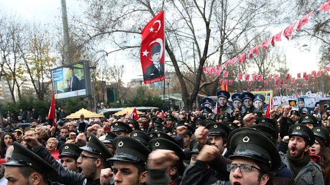 Members of Turkey's Union of Youths gather for a rally commemorating the 84th anniversary of the death of Mustafa Fehmi Kubilay, depicted in posters at right, a teacher and pro-secular lieutenant slain by Islamists who were calling for the restoration of the Sharia, in Ankara, Turkey, Saturday, Dec. 27, 2014. They also condemned the government and a massive corruption and bribery scandal that led to the resignations of four cabinet ministers last year. (AP Photo/Burhan Ozbilici)