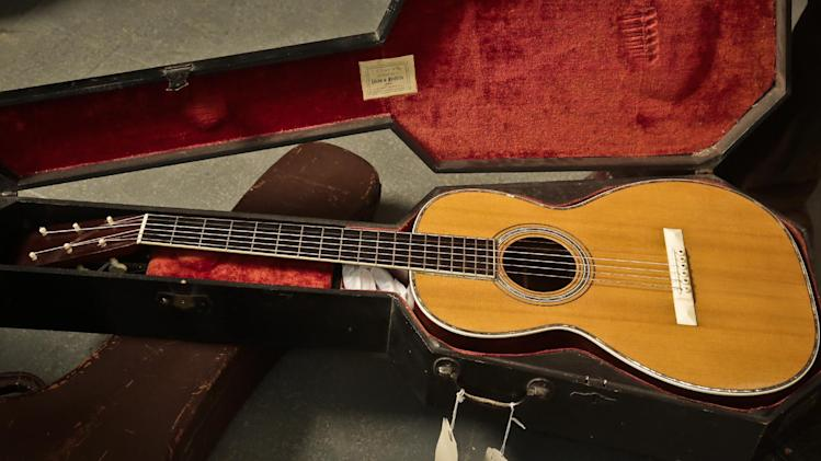 "A 1893 Martin guitar in a ""coffin"" case is unveiled during a press preview, Wednesday March 5, 2014 in New York. The guitar is among a collection of 265 extremely rare guitars from a single individual that will auction at Guernsey's on April 2 and 3. (AP Photo/Bebeto Matthews)"