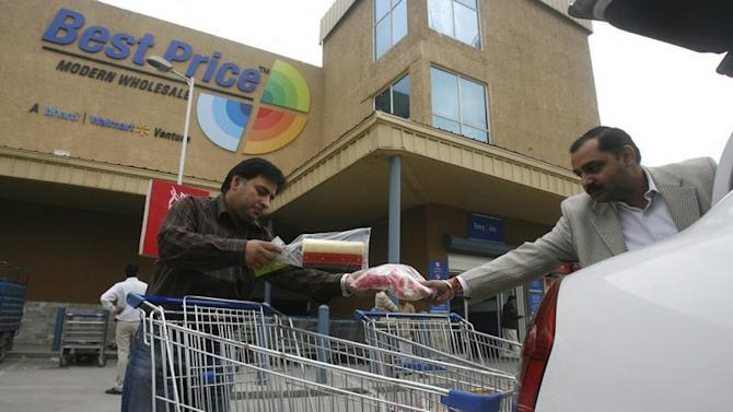 Customers load consumable goods in their car's boot after shopping at a Best Price Modern Wholesale store in Punjab