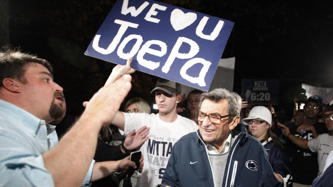 """Scott Paterno, left, looks on as students greet his father Penn State football coach Joe Paterno as he arrives at his home, Tuesday, Nov. 8, 2011, in State College, Pa. Paterno's support among the Penn State board of trustees was described as """"eroding"""" Tuesday, threatening to end the 84-year-old coach's career amid a child sex-abuse scandal involving a former assistant and one-time heir apparent. (AP Photo/Matt Rourke)"""