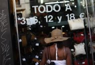 A tourist browses the window display of a store that advertises all its products for 3,6,12 and 18 euros in downtown Madrid
