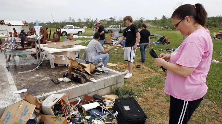 Carla Arendal looks at some jewelry she salvaged from her home on Tuesday, April 26, 2011, after a tornado destroyed the building in Vilonia, Ark. Arendal and her husband, Jay, were in the home during the storm and survived unhurt. (AP Photo/Mark Humphrey)