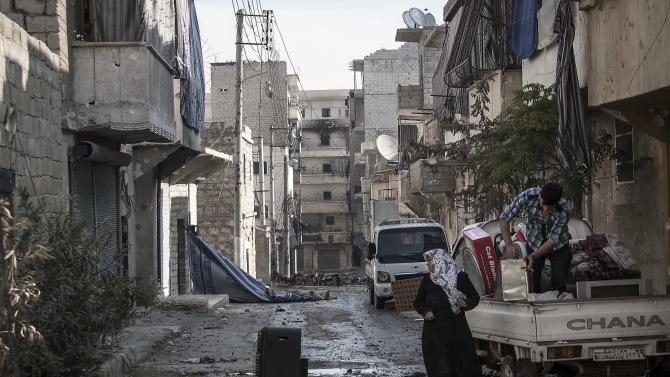 In this Sunday, Dec. 2, 2012 photo, residents collect their belongings after their home was damaged due to heavy fighting between Free Syrian Army fighters and government forces in Aleppo, Syria. (AP Photo/Narciso Contreras)