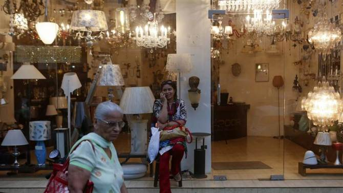 A woman speaks on a phone outside a lighting store on a street in Mumbai