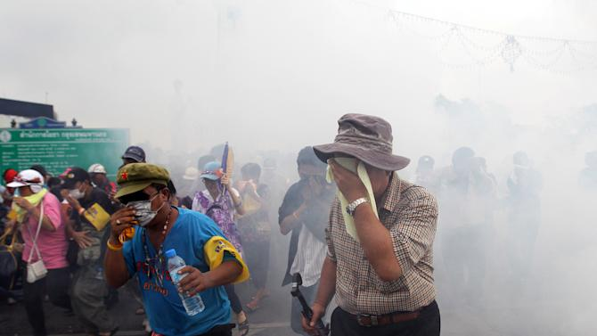 Anti-government protesters calling for Thai Prime Minister Yingluck Shinawatra to step down, protect their eyes as police fired tear gas to disperse them in Bangkok Saturday, Nov. 24, 2012. The anti-government protesters launched a rally in Bangkok on Saturday that authorities fear will grow into the biggest demonstration the country has seen since she took office last year.  (AP Photo/Sakchai Lalit)