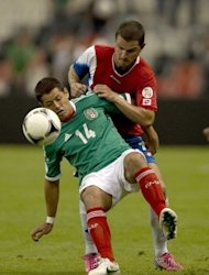 Costa Rica's Gabriel Badilla (R) and Mexico's Javier Hernandez fight for the ball during their World Cup CONCACAF qualifying match on September 11. Mexico have secured top spot in Group B with 12 points with two games left ahead of El Salvador on 5 points and Costa Rica on 4