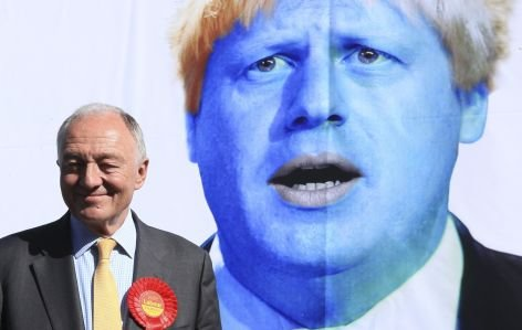 Britain's Labour candidate for London Mayor, Ken Livingstone stands in front of a poster depicting London Mayor Boris Johnson as an alien, to launch Labour's new Ad Bus in south London on April 30, 2012. REUTERS/Olivia Harris (BRITAIN - Tags: SOCIETY POLITICS)