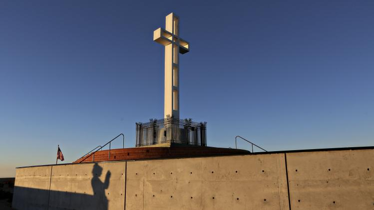 People are silhouetted against a wall as they photograph the massive cross sitting atop the Mt. Soledad War Memorial in La Jolla